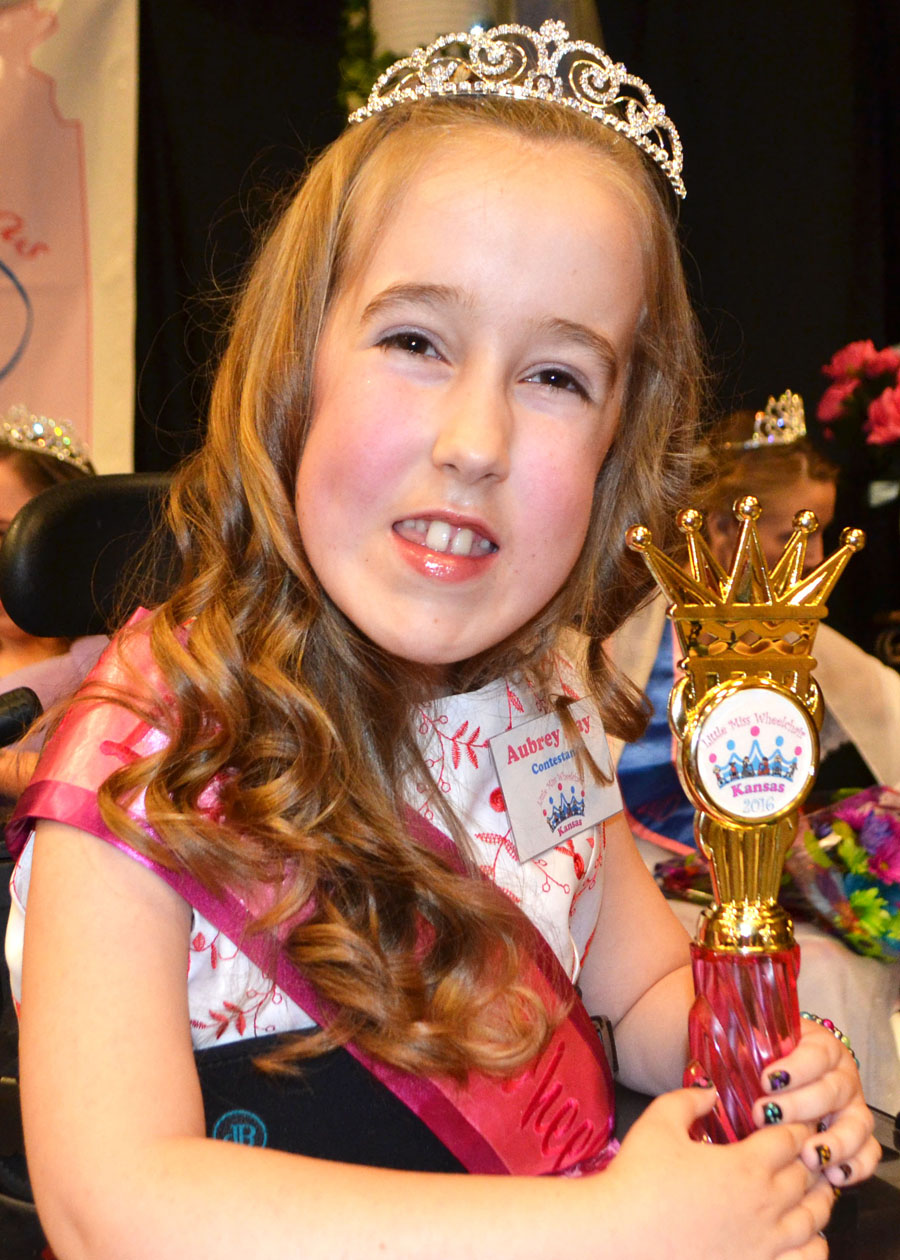 Aubrey in crown and sash holding her trophy and smiling