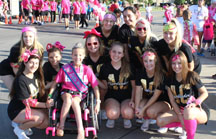 Little Miss gets a picture with cheerleaders at a community event