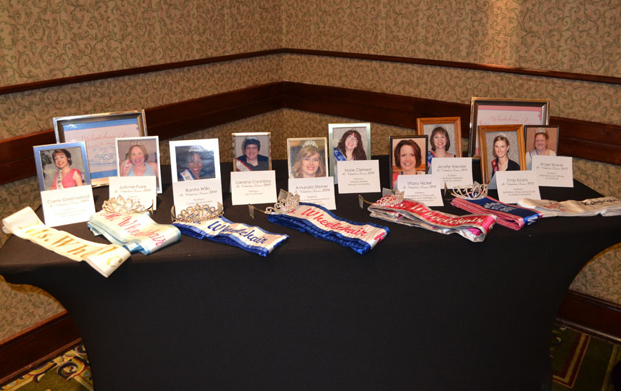 Table with former titleholder pictures, sashes, and crowns
